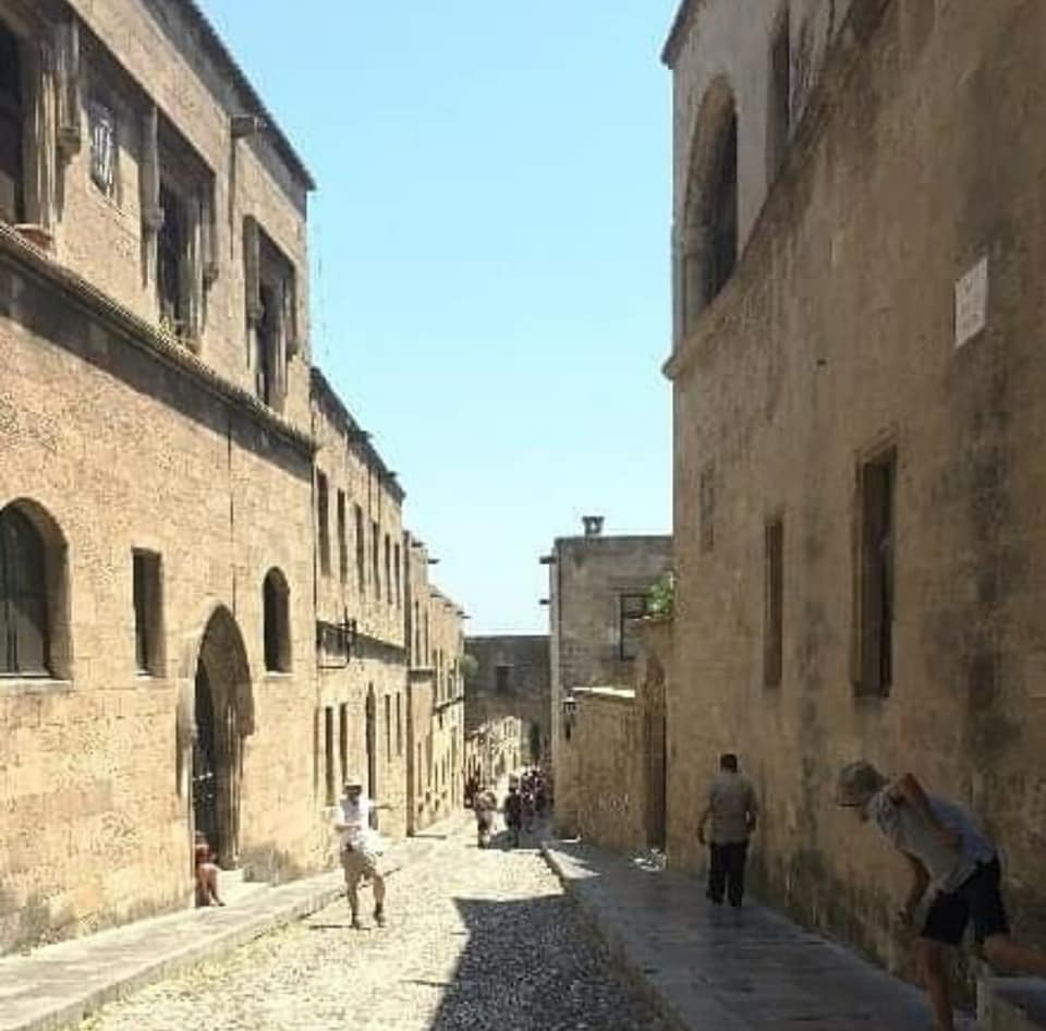A photograph of a cobbled street bordered by stone buildings. It matches, almost exactly, the street in the adjacent D&D illustration by David Trampier.
