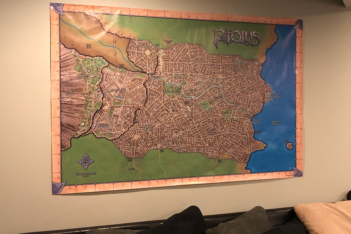 Photo of the massive vinyl map of Ptolus hung on a wall behind a sofa.