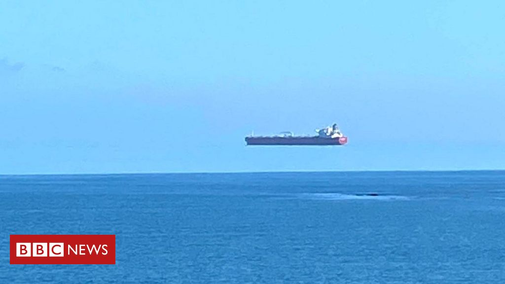 An optical illusion of a large ship at sea, apparently floating in the air high above the water.