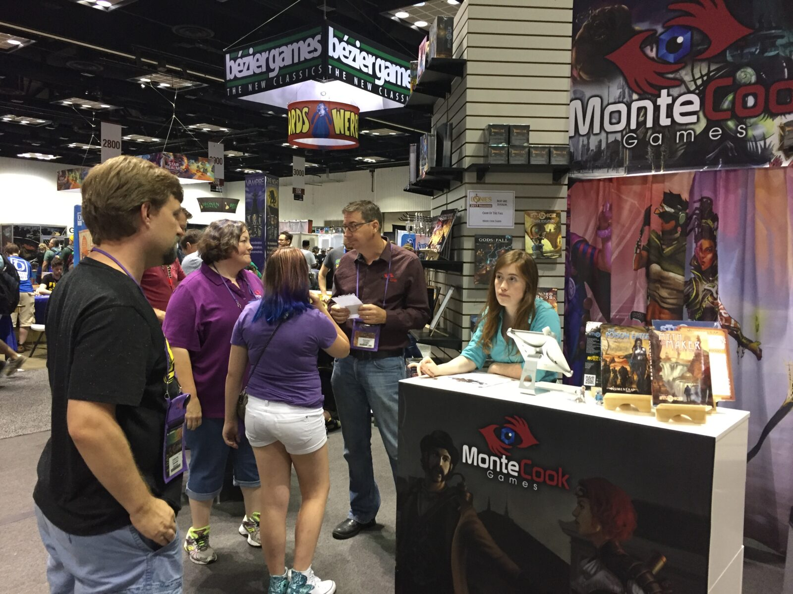 Photo from a previous Gen Con showing the MCG booth, with Andrew Cady, Zoa Smalley, Olivia Ryan, Charles Ryan, and Tammie Ryan.